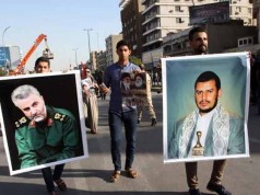Iraqi demonstrators hold up pictures of prominent Shiite leaders from Yemen and Iran in March 2015.